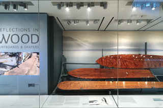 """Installation view of """"Reflections in Wood – Surfboards & Shapers"""""""