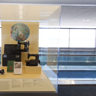 """Installation view of """"Threading the Needle: Sewing in the Machine Age"""""""