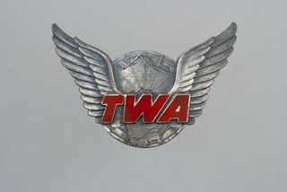 gate agent hat badge: TWA (Trans World Airlines)