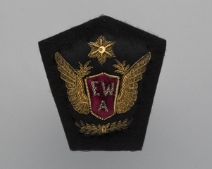 flight officer cap badge: East-West Airlines